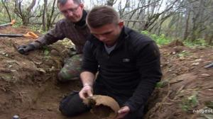 """A """"Nazi War Digger"""" team member poses with a partial cranium (image from National Geographic Channel)."""
